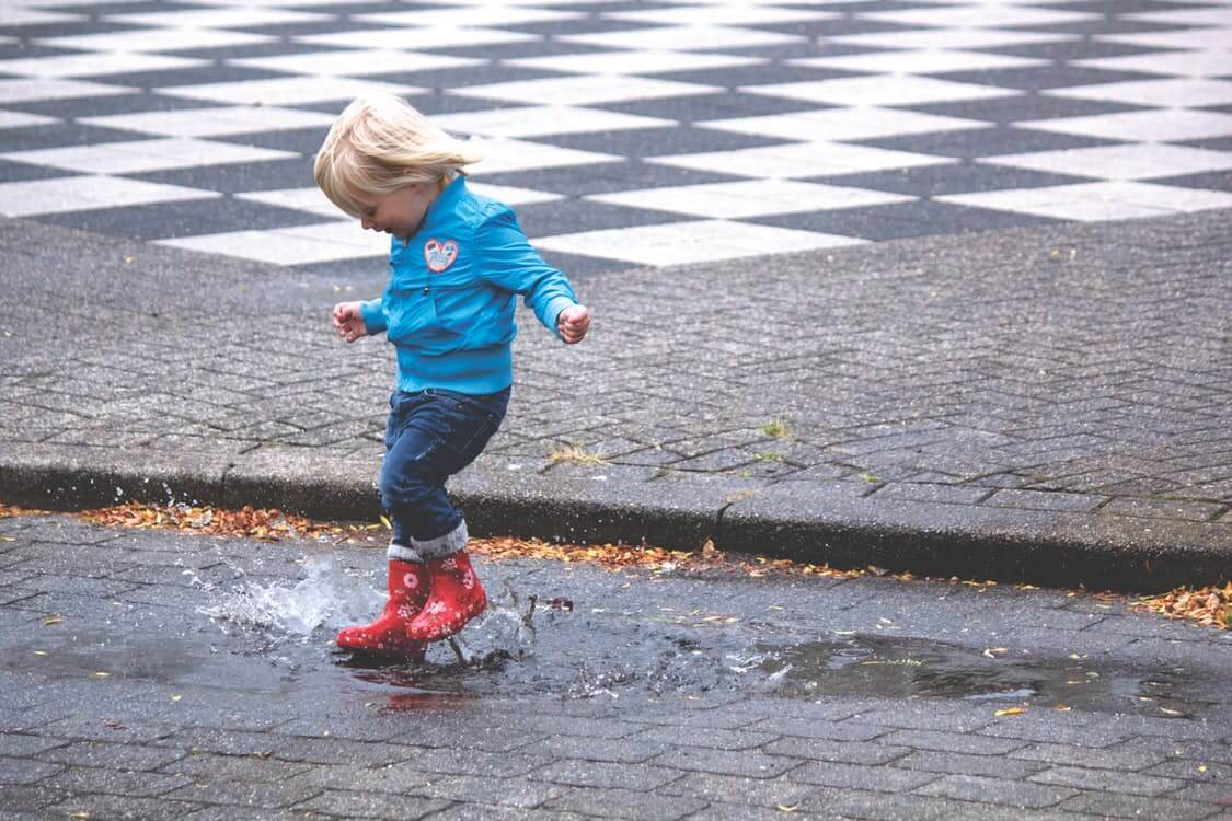 girl with rain boots jumping in puddle