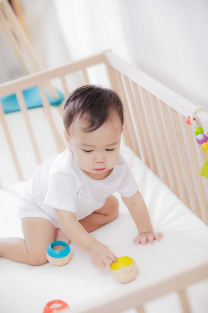 Infant playing with wooden sensory tumbling balls