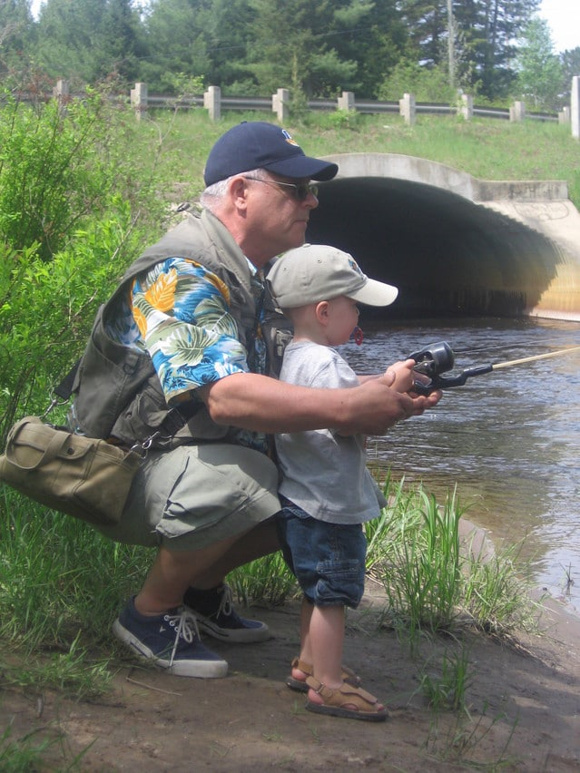 grandpa teaching toddler grandson to fish